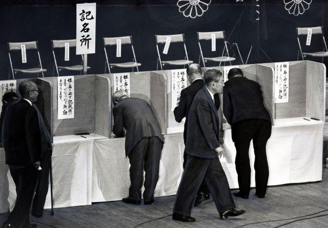 1964年7月、自民党総裁選で投票を終えた池田勇人首相(中央手前)。その後ろの「記名台」では、自民党の国会議員たちが意中の候補者名を記入。この時の会場は東京都文京区の文京公会堂だった。