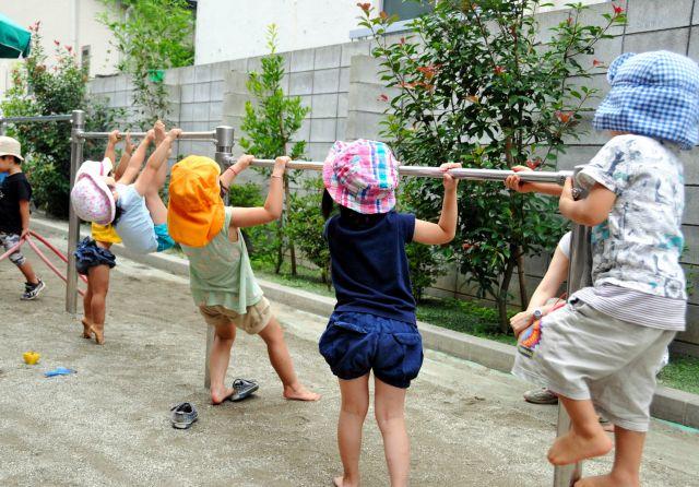 世田谷区の認可保育所で園庭にある鉄棒で遊ぶ子どもたち