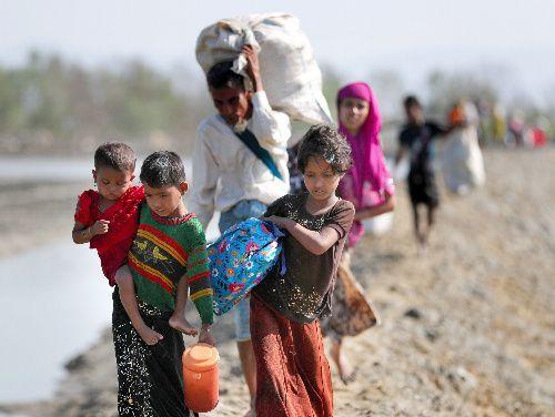 バングラデシュ南東部の国境の町テクナフで手に持てるだけの家財道具を担ぎ、ミャンマーから避難してくるロヒンギャの人たち=11月、杉本康弘撮影