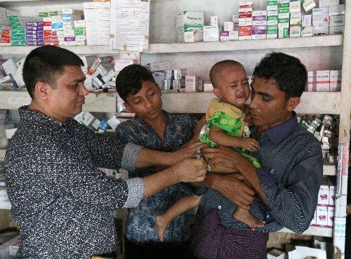 キャンプ外にある薬局で、長女ロハネスちゃんにビタミン注射を打ってもらう父親のラシッド・ウラーさん(右)=2018年8月6日、バングラデシュ南東部コックスバザール、杉本康弘撮影