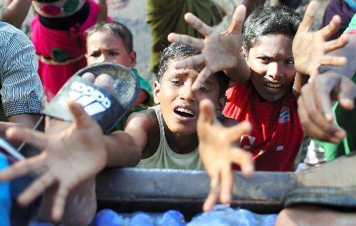 ミャンマーから逃れてきた難民が集まるバングラデシュ南東部の国境近くで、配給のために用意されたトラックの荷台にある食料と水を求める少年=2017年9月17日、バングラデシュ南東部コックスバザール