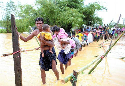 仮設テント集落が豪雨で水没し、川を懸命に渡って逃げる難民ら=2017年9月17日、バングラデシュ南東部コックスバザール