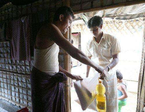 難民キャンプをまわる業者(右)に米や油などの配給物を預け現金を受け取るラシッド・ウラーさん=2018年8月6日、バングラデシュ南東部コックスバザール、杉本康弘撮影