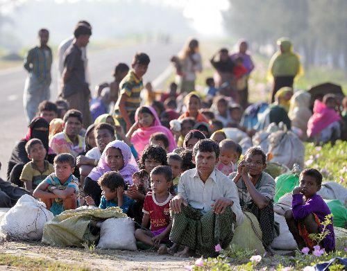 バングラデシュ南東部の国境の町テクナフで、早朝に船でミャンマーから避難してきたロヒンギャの人たち。道路脇に身を寄せ合って休んでいた=11月、杉本康弘撮影
