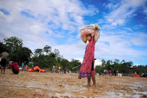 ミャンマーから逃れてきた難民たちが多く集まるバングラデシュ南東部の国境近くで、難民のテントが立ち並ぶ中を、食料の配給を受けた少女が歩いてた=2017年9月17日、バングラデシュ南東部コックスバザール