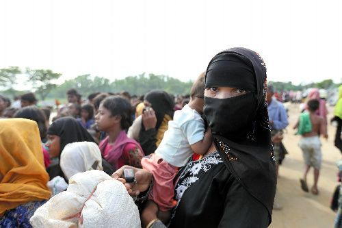 ミャンマーから逃れてきたロヒンギャ難民の女性は子どもを抱き、配給の列に並んでいた=2017年9月17日、バングラデシュ南東部コックスバザール