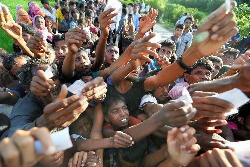 ミャンマーから逃れてきた難民が集まるバングラデシュ南東部の国境近くで、配給のために用意されたトラックの荷台にある食料と水を求める人たち=2017年9月17日、バングラデシュ南東部コックスバザール