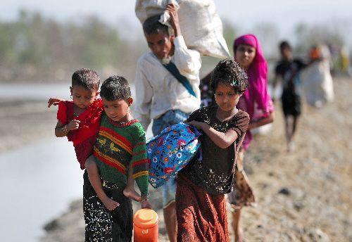 バングラデシュ南東部の国境の町テクナフで、手に持てるだけの家財道具を担ぎ、ミャンマーから避難してくるロヒンギャの人たち=2017年11月20日