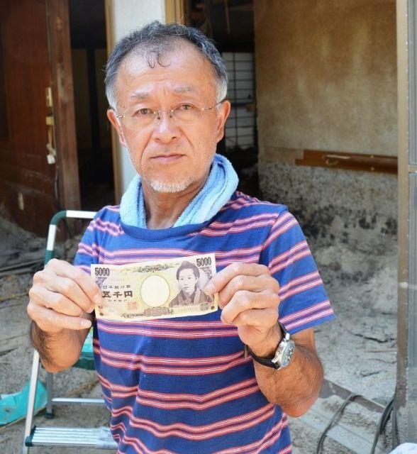 5000円札を見せる高下(こうげ)博美さん=広島県坂町小屋浦4丁目