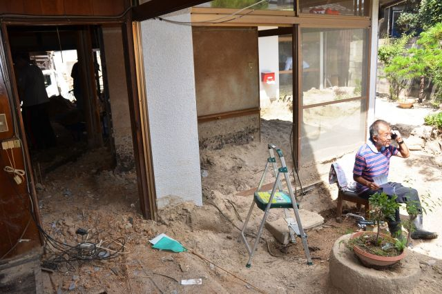 ボランティアが土砂を撤去してもらう横で、様々な手続きに忙しい高下(こうげ)博美さん=広島県坂町小屋浦4丁目