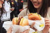 「おいしい!」とご当地バーガーをほおばる若者たち=北九州市