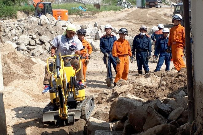 兵庫県から自前の重機を持ってやってきたボランティアが、機材の足りない遺体捜索現場の土砂撤去を手伝っていた=8月、広島県坂町小屋浦