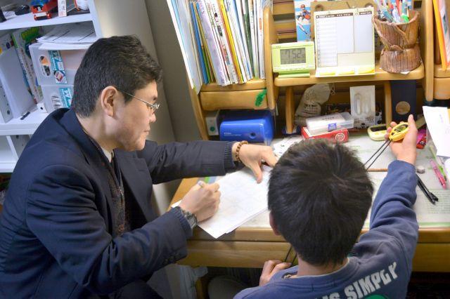 男子中学生(右)に授業をする家庭教師の大矢敦嗣さん。飽きさせないよう次々と教材を投入=愛知県内