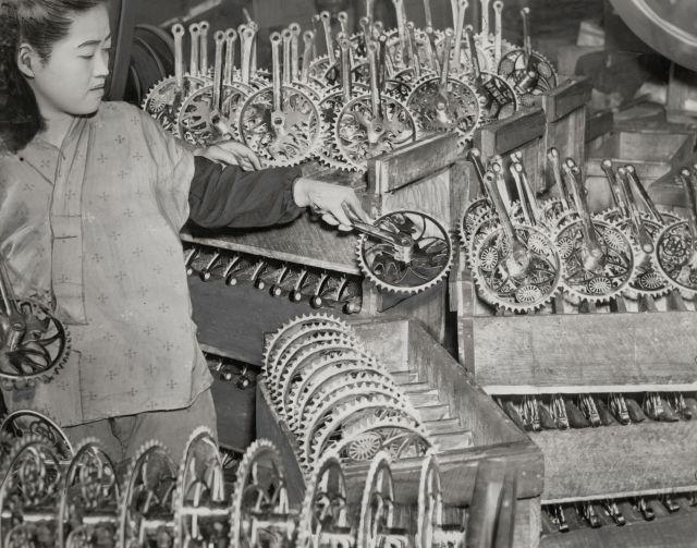 部品問屋に山積みされた自転車用のギアを管理する女性。(1952年撮影)