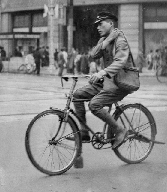 明治期以降に流行した「ダイヤモンド型」自転車に乗る郵便局員。サドルやハンドルを結ぶフレームの形が、ダイヤモンドのように見える。(1939年10月ごろ撮影)