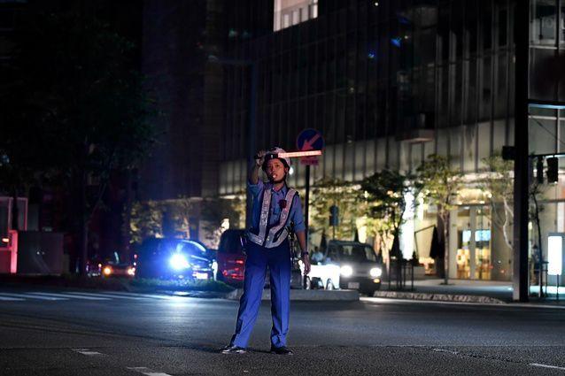 夜になっても停電が続き、警察官が交差点に立って手信号で交通整理を続けていた=2018年9月6日午後7時13分、札幌市中央区