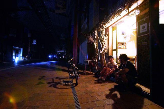 停電が続く繁華街の「狸小路商店街」で、ガスのランタンをつけながら電気の復旧を待つ人たち=2018年9月6日午後10時46分、札幌市中央区、小玉重隆撮影