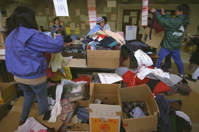 阪神大震災の避難所で被災者に贈られた衣類を仕分けするボランティアの人たち