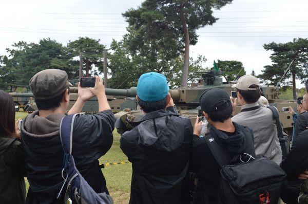 展示された戦車が砲身を動かすと若者らが集まり、熱心にスマホで撮影した。