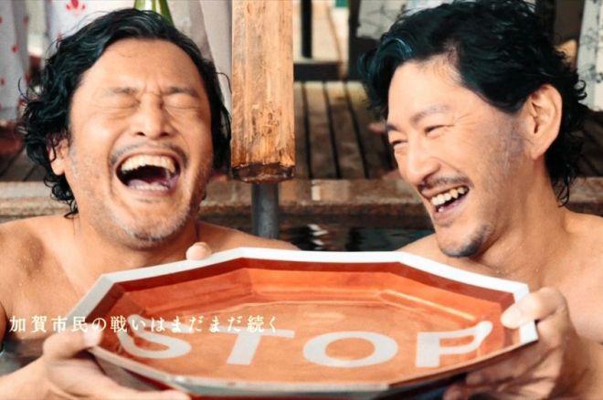 加賀と小松の温泉対決が終わり、お互いの健闘をたたえ九谷焼の「STOP皿」に注いだ酒を飲む加賀停太郎(左)と小松停太郎=石川県加賀市提供