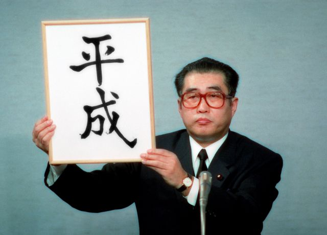新元号が書かれた額を掲げる小渕氏(1989年1月7日撮影)