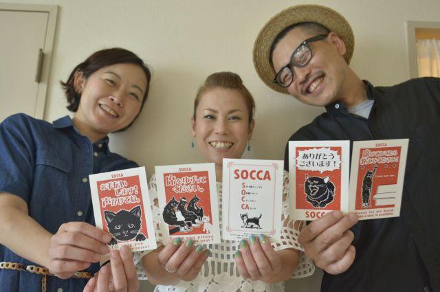 ヘルプカード「SOCCA」をUnBalanceのメンバーたちと持つ元村さん(中央)