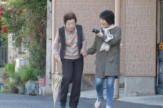 撮影しながら、外を歩く信友さん親子 🄫「ぼけますから、よろしくお願いします。」製作・配給委員会