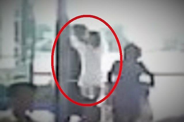 通行人の背後から両手を伸ばし、顔に「いたずら」するフォン(中央)の姿を、ハノイの空港の監視カメラは記録していた=関係者提供