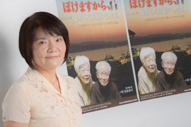 監督兼撮影兼語り、そして「ひとり娘」と映画のちらしなどに書く信友直子さん=山本和生撮影