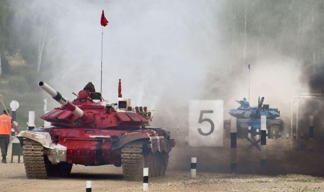 猛スピードで走る戦車。黒煙と砂ぼこりで後ろが見えなくなります=中川仁樹撮影