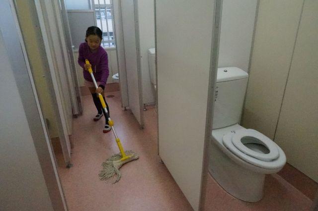 洋式便器が増え、床がタイルから「乾式」のシート張りになったトイレで、モップをかける児童=福岡市西区