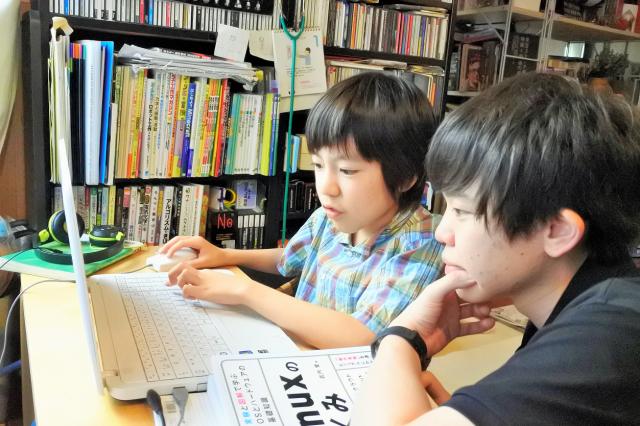 谷朋優さん(左)と梅内祐太さん。ノートパソコンのOSに言語を打ち込み、プログラムの仕組みを学んでいた=東京都内