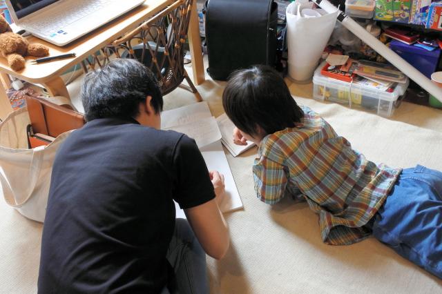 「頭の準備体操」にと、横になりながら論理パズルを解く2人。好きな姿勢で取り組めるのも自宅ならでは=東京都内