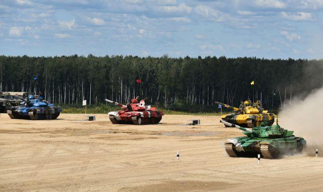 激走するカザフスタンチームの緑の戦車。後ろには、故障などにそなえた予備の戦車が止まっています
