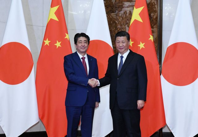 会談を前に握手する安倍晋三首相(左)と中国の習近平国家主席=10月26日、北京の釣魚台国賓館、代表撮影