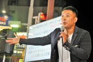 Tシャツにジャケット姿。大きな身ぶりで訴える=10月9日、千葉・船橋駅