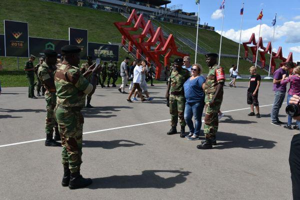 「戦車バイアスロン」会場でジンバブエ軍の兵士と記念撮影をする観客。国際交流も大会の重要な目的の一つ