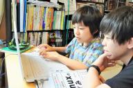 コンピューターのシステムについて、「先生」の梅内祐太さんから教えてもらう谷朋優さん(左)=東京都内