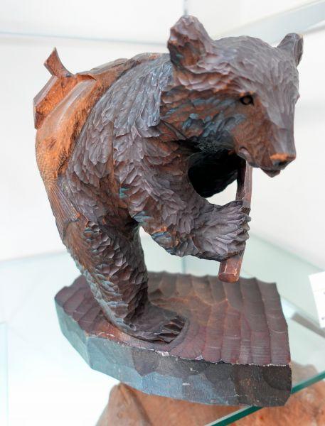 1957年に制作された、アイヌ民族の床ヌブリ(1937~2014)の作品。シャケを背負っている=北海道八雲町の町木彫り熊資料館