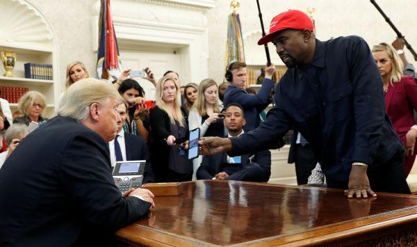 ワシントンにあるホワイトハウスの大統領執務室で2018年10月、トランプ大統領(左)に自身のスマートフォンを見せるカニエ・ウエスト