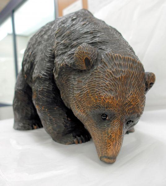 日本画家でもあった十倉金之(1883年生まれ)の木彫り熊。肩の部分が盛り上がり、そこから四方に毛が流れる「菊型毛」を考案した。繊細な毛を彫った木彫り熊の見本となった=北海道八雲町の町木彫り熊資料館