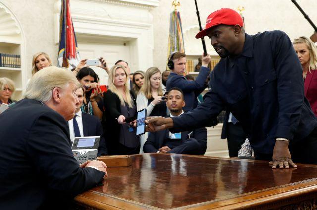 ワシントンにあるホワイトハウスの大統領執務室で2018年10月、トランプ大統領(左)に自身のスマートフォンを見せるカニエ・ウエスト=ロイター