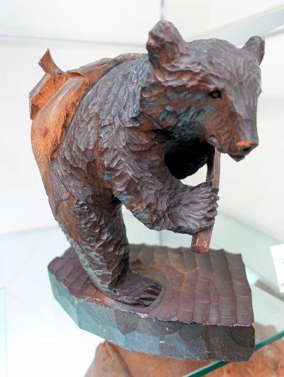 1957年に制作された、アイヌ民族の床ヌブリ(1937~2014)の作品。サケを背負っている=北海道八雲町の町木彫り熊資料館