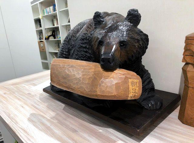 朝日新聞をくわえた木彫り熊=札幌市の朝日新聞北海道支社