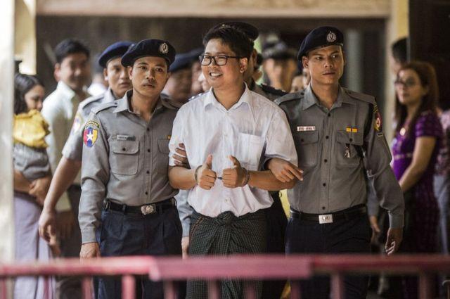 報道陣に笑顔を向け、法廷に入るワローン氏。拘留中に生まれた子どもとは、裁判の時しか顔を合わせられない=2018年9月、ミャンマー・ヤンゴン