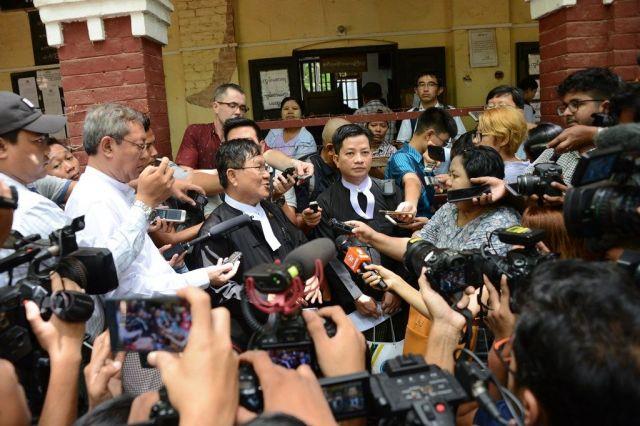 予審裁判後、報道陣に囲まれる、ワローン氏らの弁護士(中央2人)。検察側の主張の矛盾を指摘し続けた=2018年4月、ミャンマー・ヤンゴン