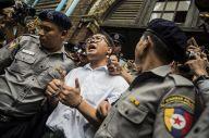 懲役7年の実刑判決を受けた、ロイター通信のワローン記者(中央)。逮捕直後から一貫して無実を訴えている=2018年9月、ミャンマー・ヤンゴン