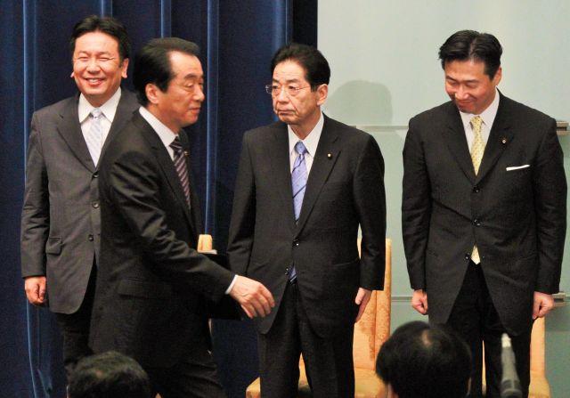 退陣の記者会見を終え退出する菅直人首相(左から2人目)。中央は仙谷由人官房副長官=2011年8月、首相官邸