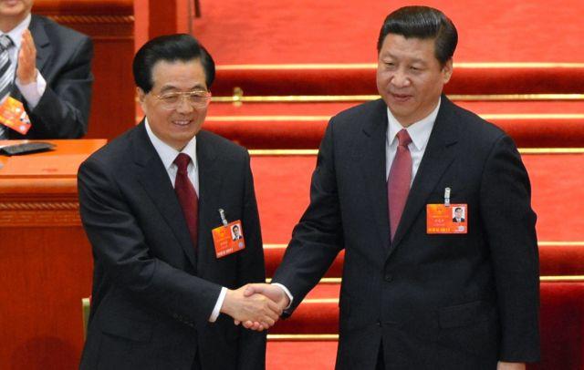 北京の人民大会堂で国家主席に選出され、胡錦濤前主席(左)と握手する習近平総書記=2013年3月