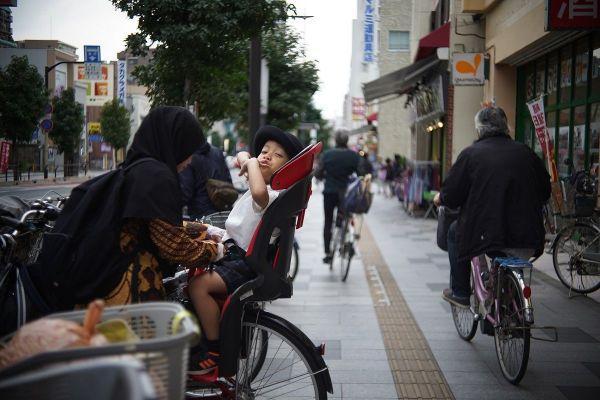 日本の子育てで欠かせないママチャリ。宗教上、長いスカート姿だが、下には長いズボンをはいてめくれないよう対策済みだ